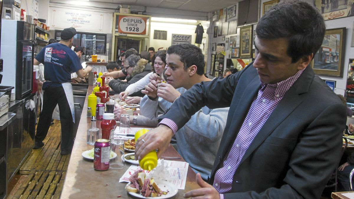 Mohsen Khlifi puts mustard on his smoked meat sandwich prepared at Schwartz's deli on St. Laurent in Montreal