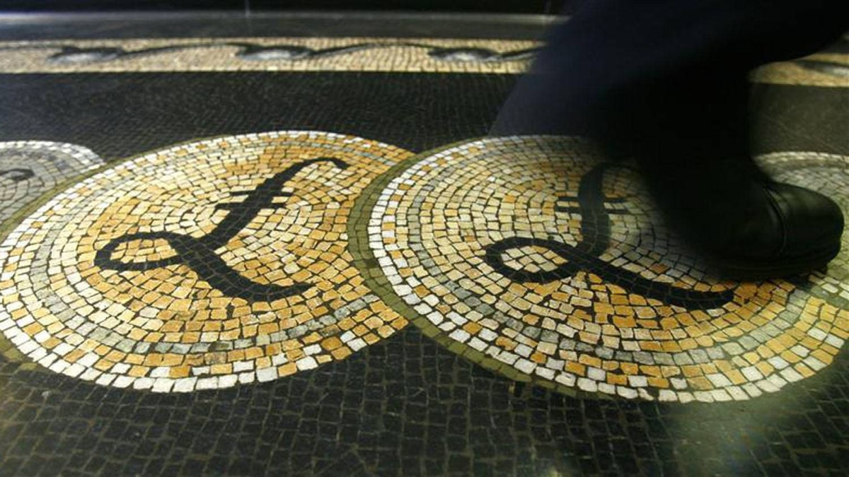 An employee is seen walking over a mosaic of pound sterling symbols set in the floor of the front hall of the Bank of England, in London in this March 25, 2008 file photograph.