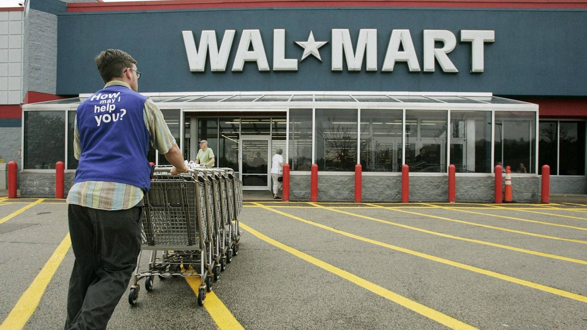 A Wal-Mart employee pushes a line of shopping carts toward the entrance of a Wal-Mart store, in Walpole, Mass., in this file photo.