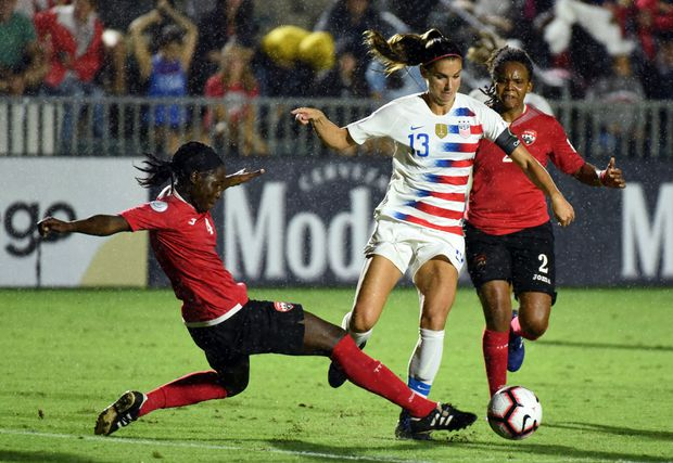 ed41033a07d United States forward Alex Morgan avoids the tackle of Trinidad and Tobago  defender Rhea Belgrave during the first half of a 2018 CONCACAF Women s ...