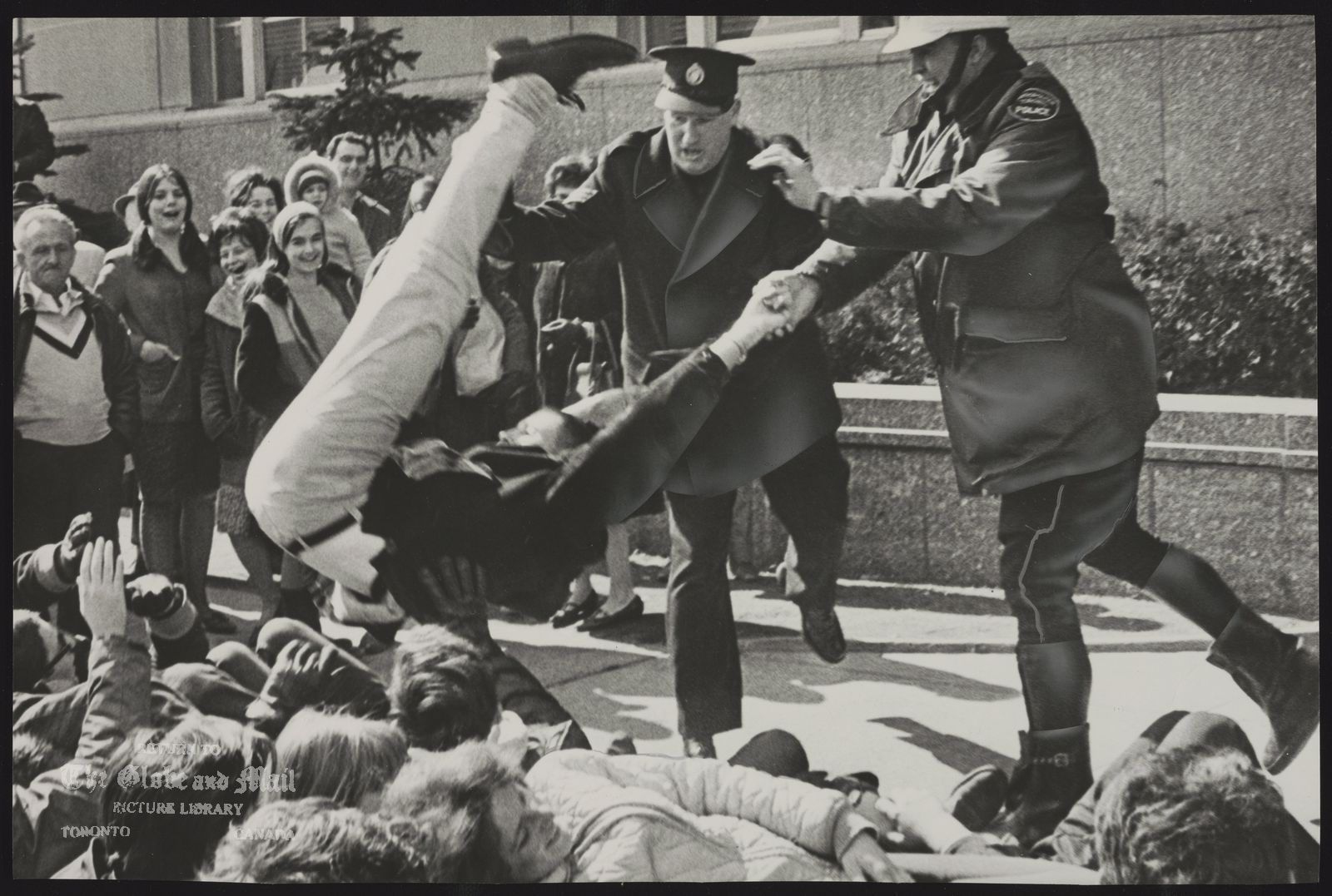 The notes transcribed from the back of this photograph are as follows: Demonstrations Racial Patrol Sgt. Donald Dodgson and Constable Thomas Moclair put their backs into it as they toss a student in Toronto back to the curb.
