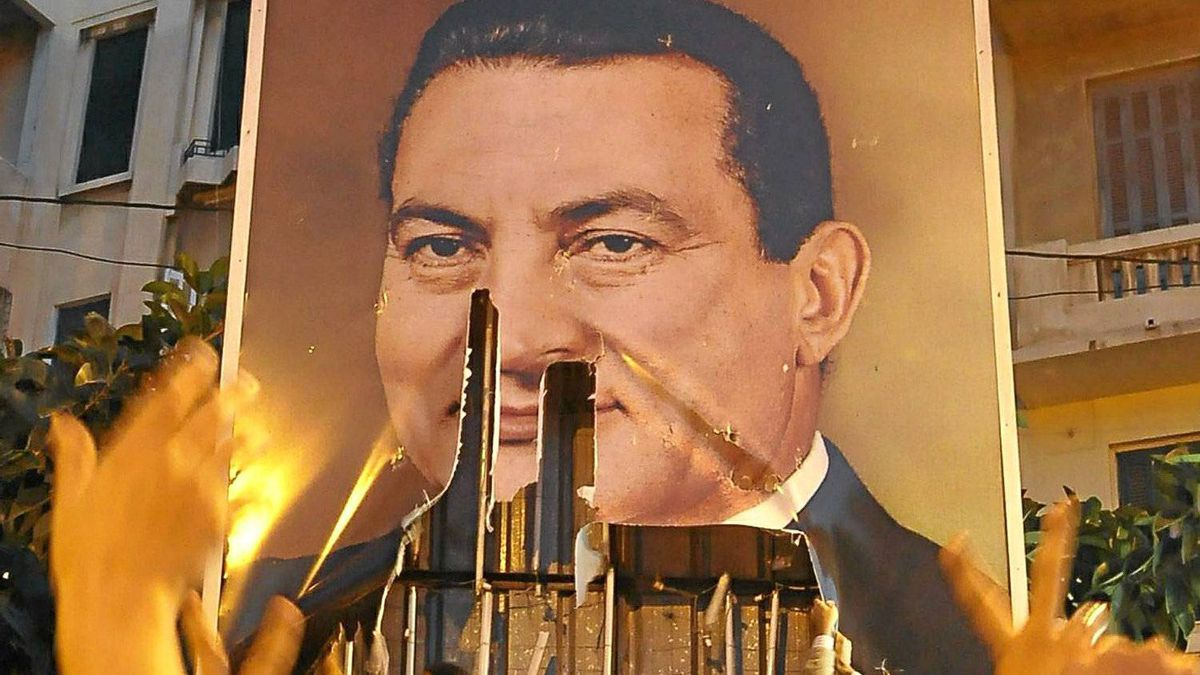 Egyptian demonstrators tear a portrait of President Hosni Mubarak during a protest against his rule in the northern port city of Alexandria on January 25, 2011. AFP PHOTO/STR
