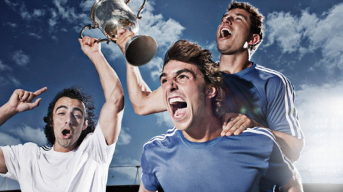Soccer players cheering with trophy