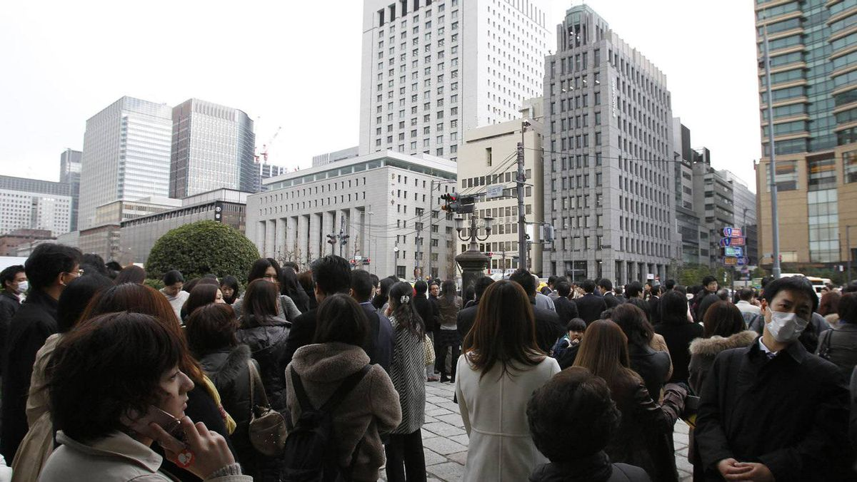 People stand in the street after evacuating buildings in Tokyo's financial district.