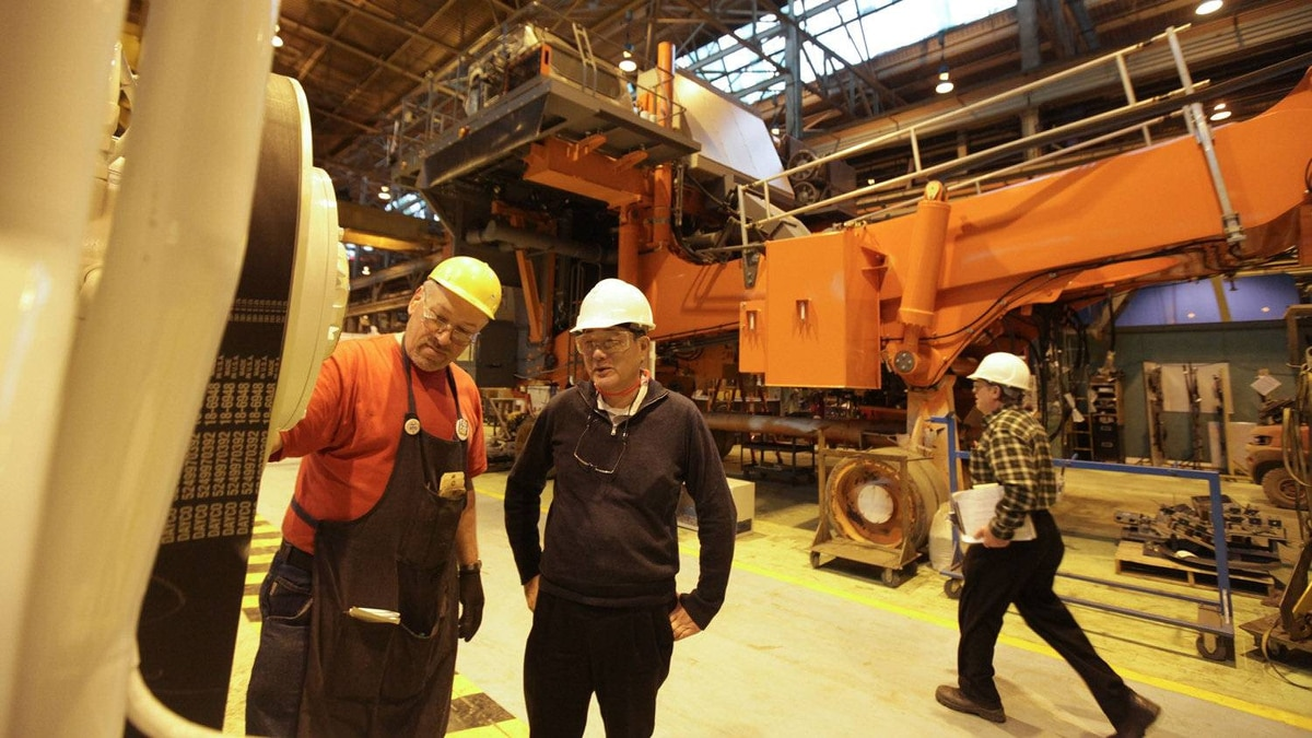 Hideo Kitawaki, centre, CEO of Hitachi Construction Truck Manufacturing Ltd., talks with engine assembler Ralph Schmidt, left, near one of their 3,000 horsepower motors used in dump trucks. Mr. Kitawaki said the company would like to increase its global market share for giant mining trucks to 40 per cent from 8 per cent now.