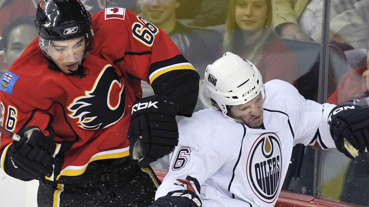 Calgary Flames T.J Brodie (L) hits Edmonton Oilers Colin Fraser against the boards during the second period of their pre-season NHL hockey game in Calgary, Alberta, October 3, 2010. REUTERS/Todd Korol