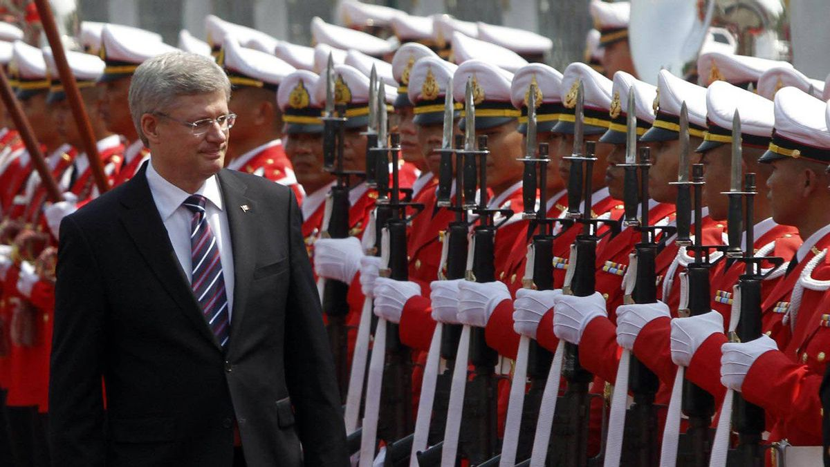 Prime Minister Stephen Harper reviews an honour guard during a welcoming ceremony at the Government House in Bangkok on March 23, 2012.