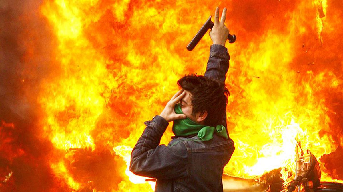 An Iranian opposition supporter gestures next to a burning police motorcycle set on fire during clashes with security forces in Tehran on Dec. 27, 2009.