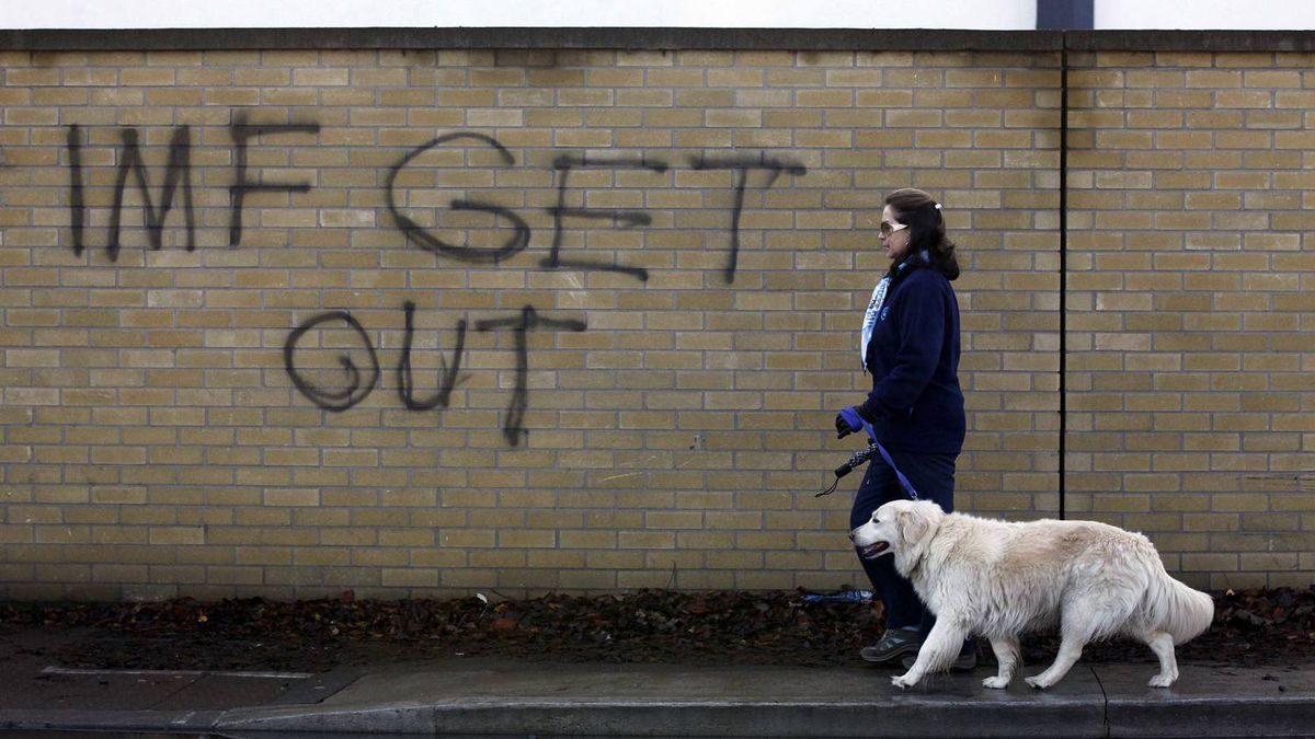 A woman walks her dog past a graffiti in South Dublin November 23, 2010. The adoption of the Irish 4-year austerity programme and the 2011 budget in particular is key for the EU/IMF financial support programme for Dublin now under negotiations, the European Commission said on Tuesday.