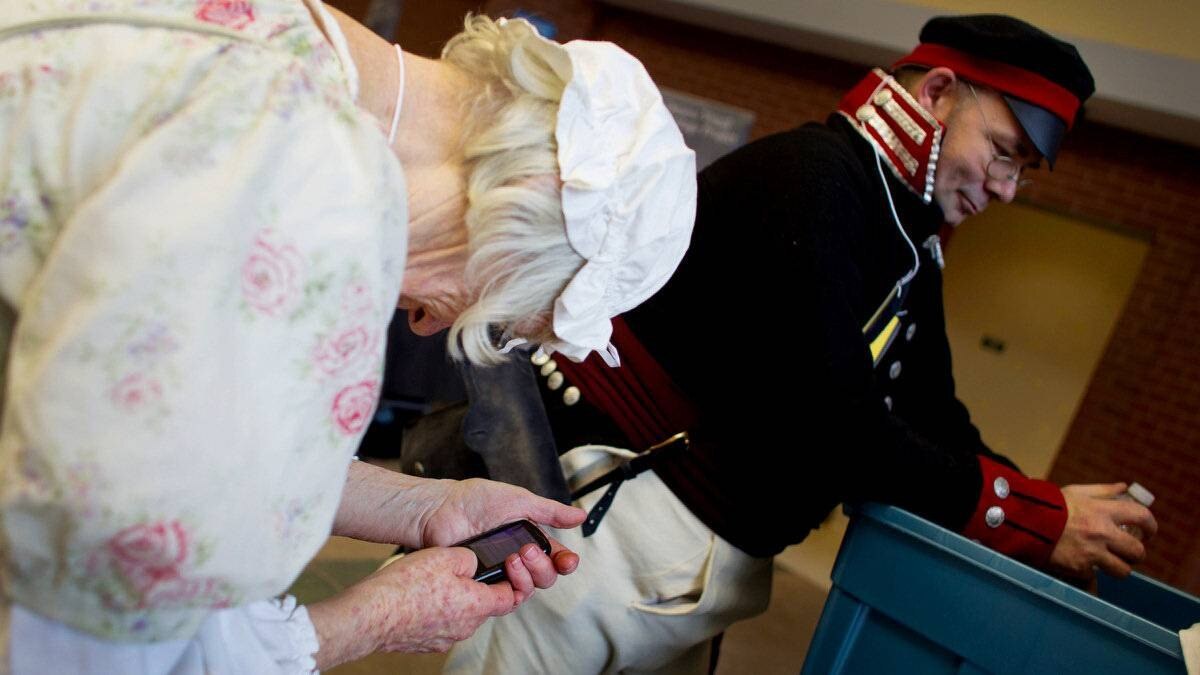 Peg Kellins, of Clinton, Ont., checks her mobile phone during a break from weaving. At right, Paul Watson, of Clifford, Ont., is dressed as a soldier from the 21st U.S. Infantry.