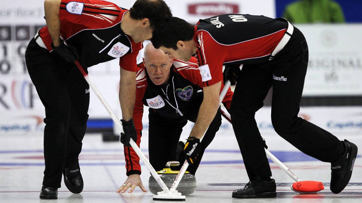Ontario skip Glenn Howard, centre, watches his shot as second Brent Laing, left, and lead Craig Savill sweep during a morning draw against British Columbia at the Tim Hortons Brier in Saskatoon, March, 7, 2012.