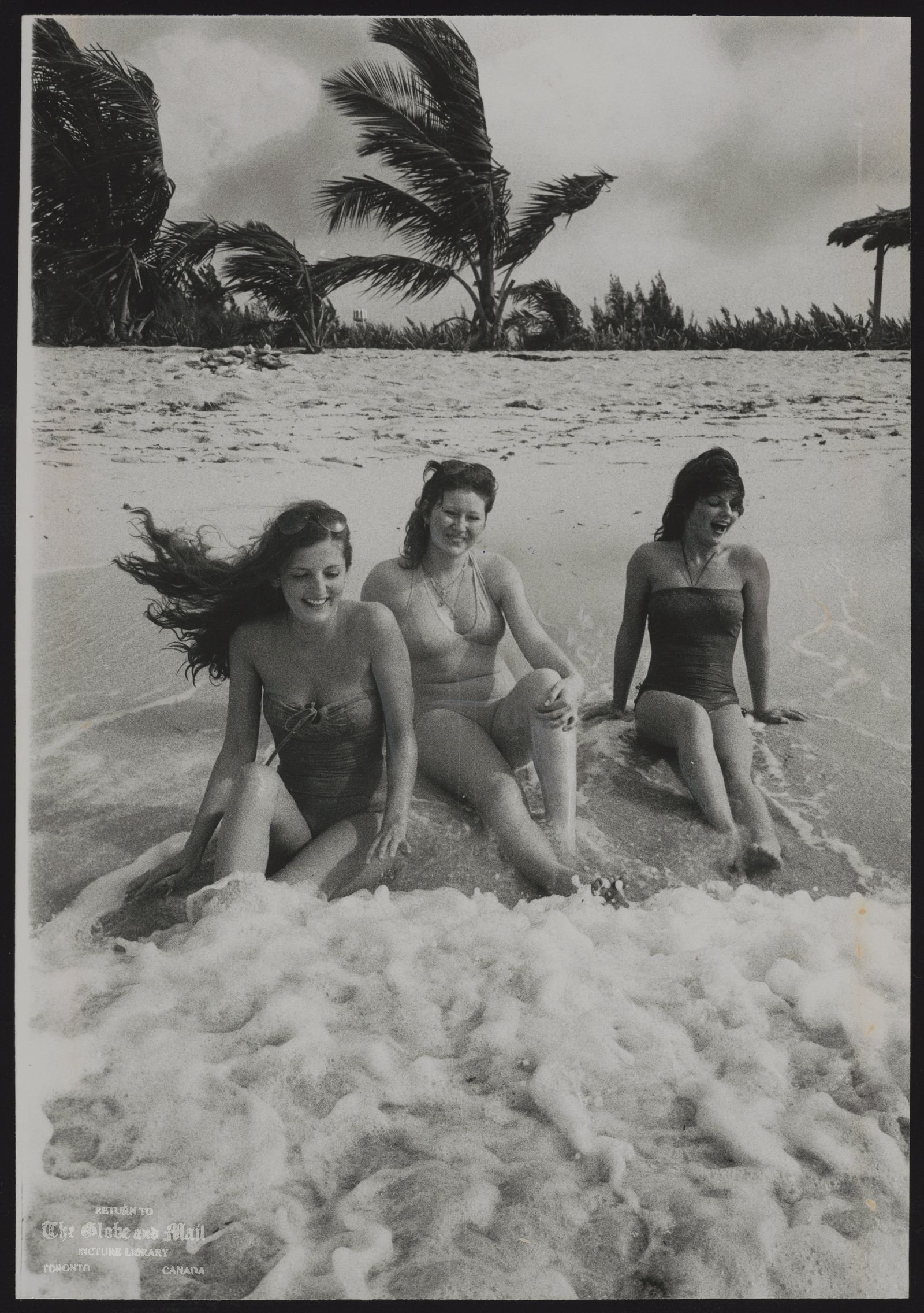 BAHAMAS Sitting in the surf on a Bahamian beach, Sally Thornton, left, her sister Janette, right, and Kelley Durling are not missing Christmas snow and ice of New Brunswick.