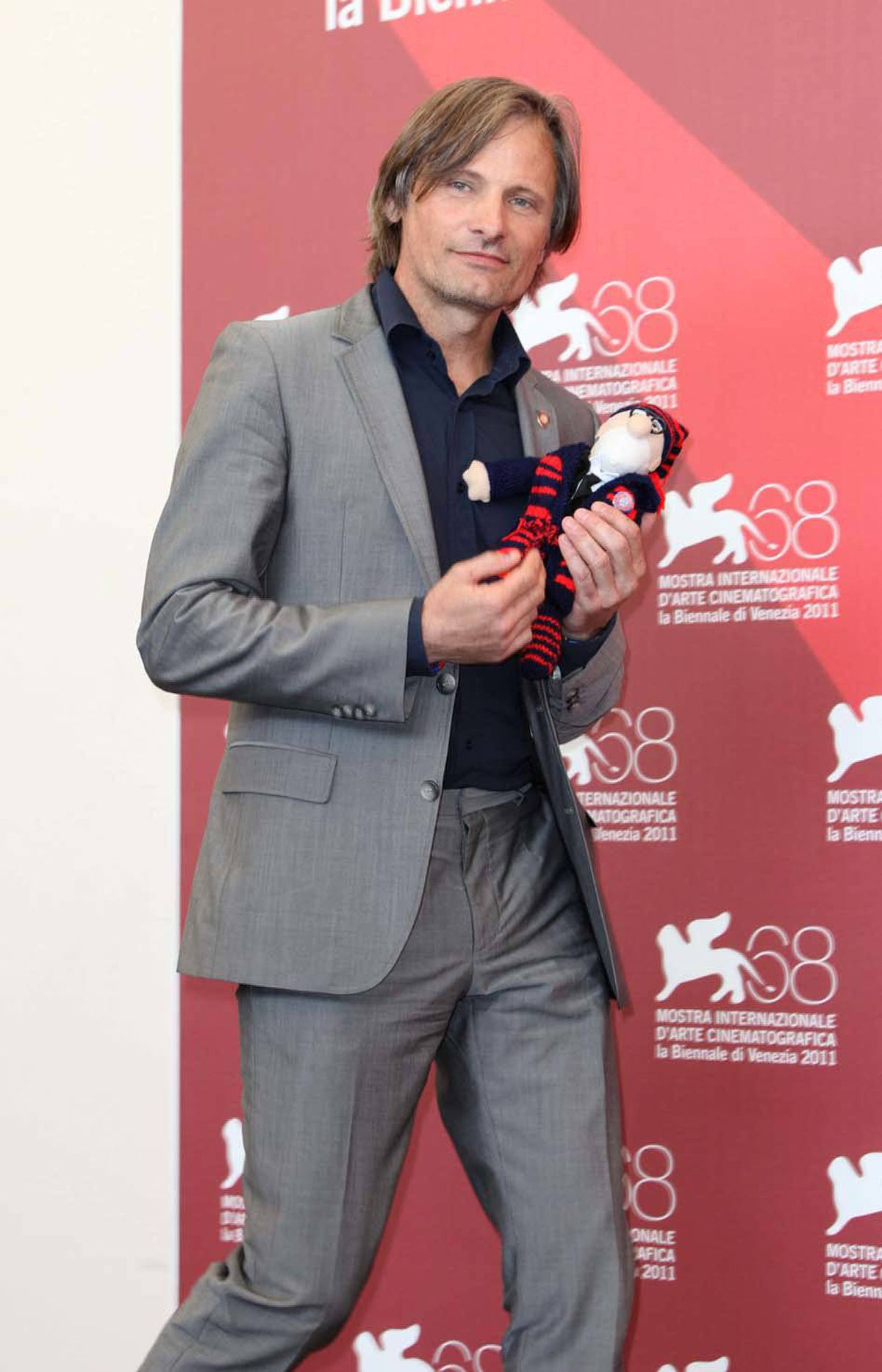Danish actor Viggo Mortensen poses with a doll given to him by a fan at the Venice Film Festival on Friday.