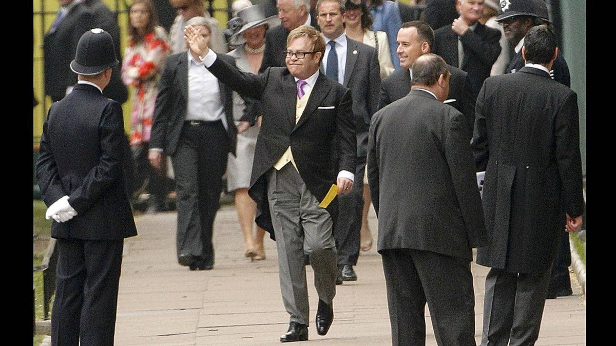 Sir Elton John waves as he arrives at Westminster Abbey before the wedding of Britain's Prince William and Kate Middleton, in central London April 29, 2011.