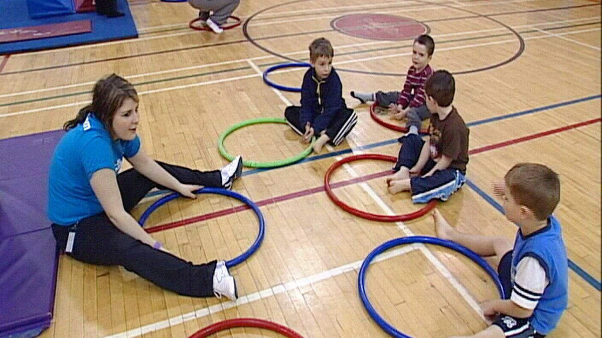 A Go-Go gymnastics coach does a warm-up with children using hula hoops.