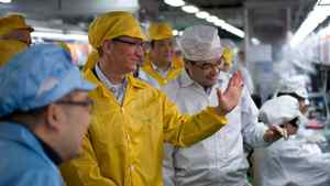 Apple Chief Executive Officer Tim Cook talks to employees as he visits the iPhone production line at the newly built Foxconn Zhengzhou Technology Park, Henan province, in this March 28, 2012 file handout photo. Apple said March 29, 2012 it had agreed to work with partner Foxconn to substantially improve wages and working conditions at the factories that produce its products.