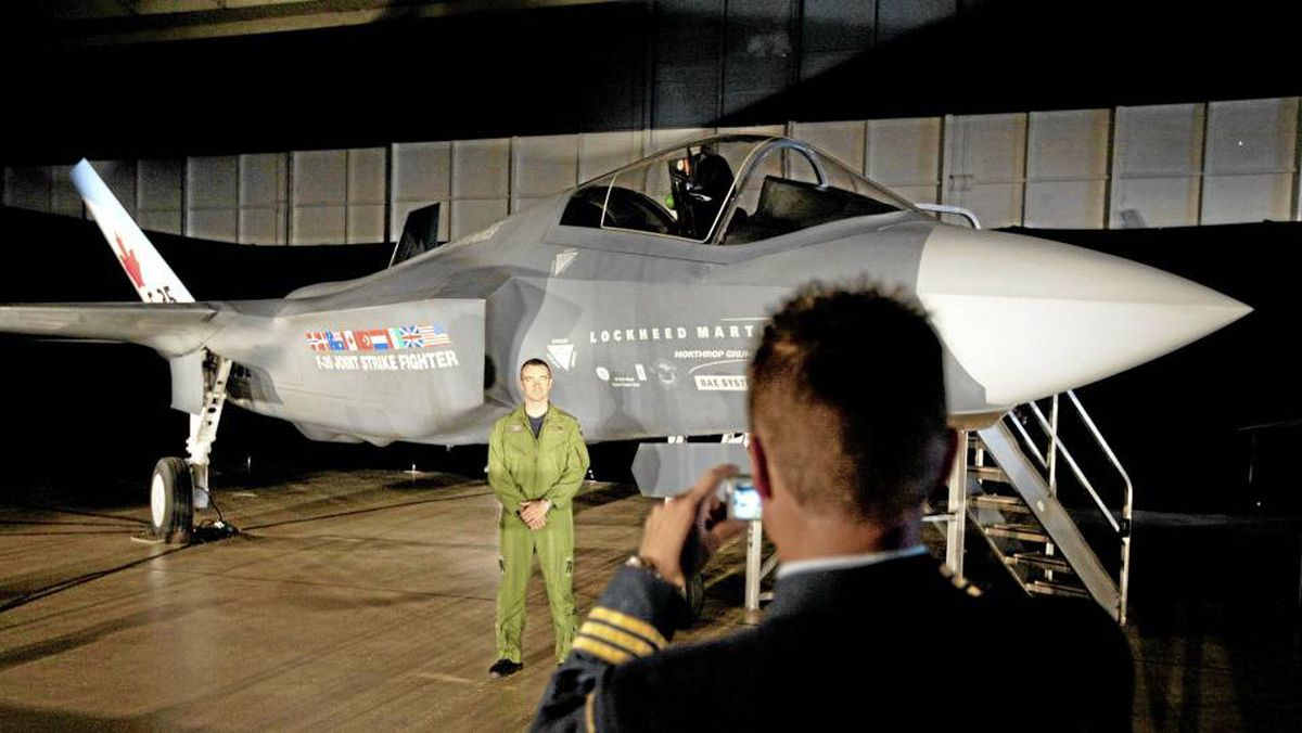A Canadian Forces pilot has his picture taken in front of a F-35 fighter mock-up prior to a procurement announcement in Ottawa on July 16, 2010.