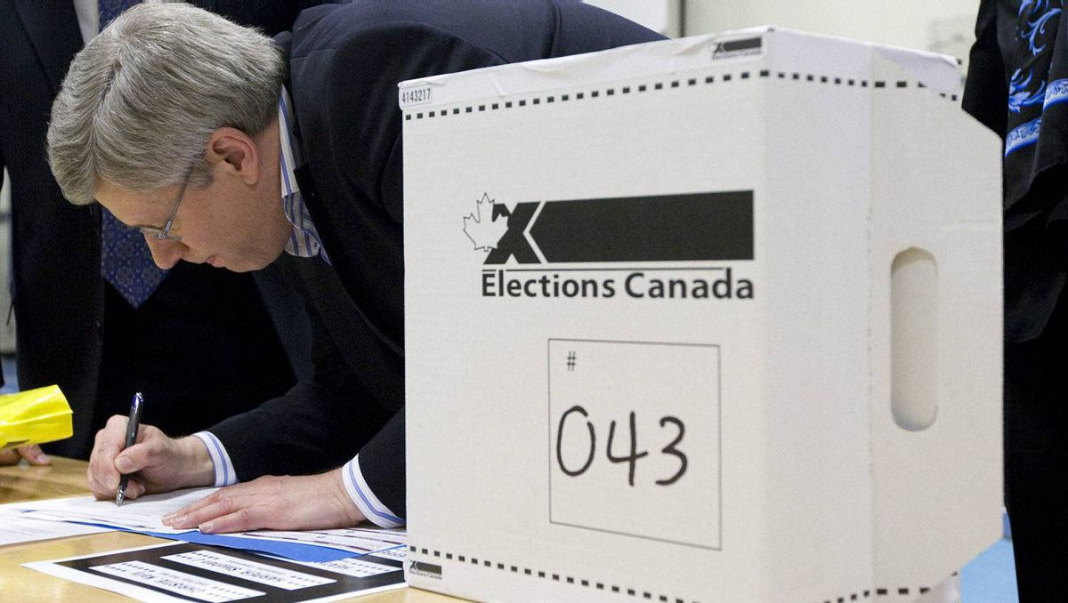 Prime Minister Stephen Harper signs a form as he casts his ballot in Calgary, Alta., Monday May 2, 2011.