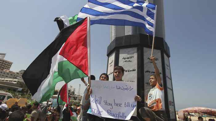 Palestinians hold flags during a rally in support of a Gaza-bound flotilla, at the Gaza seaport July 3, 2011.