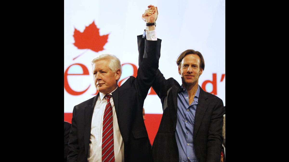 Bob Rae raises the hand of the new Liberal Party President, Mike Crawley, right, at the end of the Liberal Convention in Ottawa on Jan. 15, 2012.