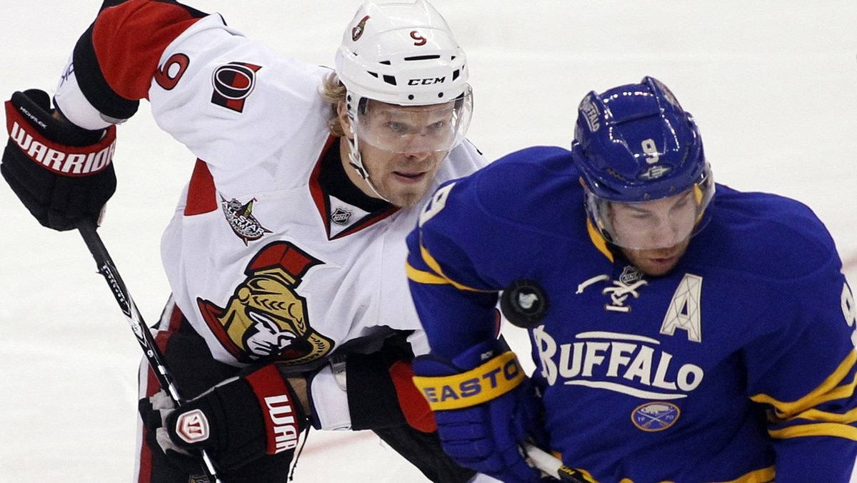 Ottawa Senators' Milan Michalek (L) watches the puck hit Buffalo Sabres' Derek Roy during the first period of their NHL hockey game in Ottawa November 5, 2011. REUTERS/Blair Gable