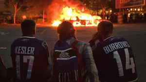 Vancouver Canucks fans watch police cars burn after Game 7 of the NHL Stanley Cup hockey playoff
