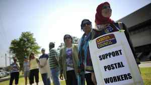 Canadian Union of Postal Workers (CUPW) members stand in front of a Canada Post sorting facility in Toronto, June 15, 2011.