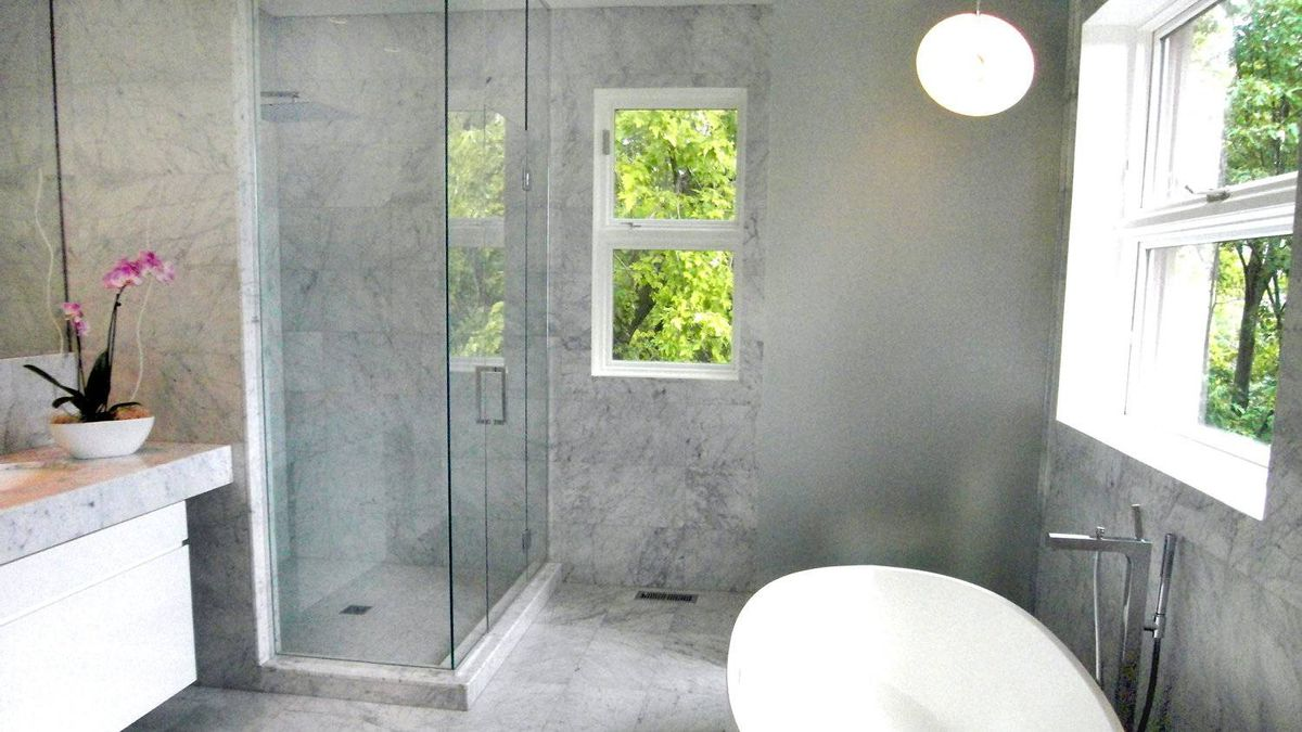 The master bathroom features grey and white marble, heated floors and freestanding tub by Quebec-based Wetstyle.