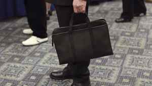 A man holds his briefcase at a job fair in New York last month. The broad and deep decline in public hiring is a significant shift in the United States labour market.
