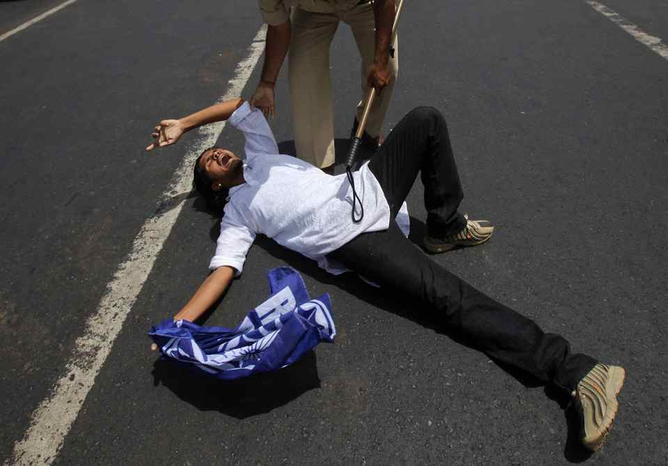 A demonstrator shouts slogans while lying on a highway as a policeman tries to detain him during a protest against the hike in petrol prices in Mumbai , India.
