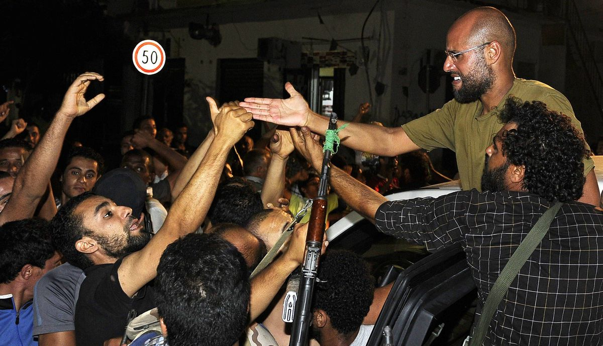 Saif Al-Islam, son of Moammar Gadhafi, greets supporters in Tripoli August 23, 2011. Saif al-Islam al-Gadhafi is the former dictator's second eldest son and arguably the most charismatic. His whereabouts are unknown and there are conflicting reports that he has been captured or that he is still at large inside Libya. He was seen as a reformer. However, during the Libyan uprising he became the public face of the regime during its crackdown on protests.