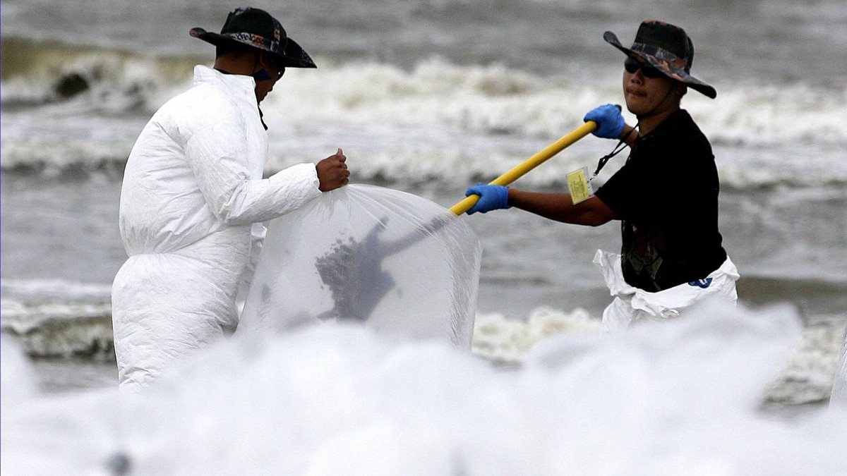 Oil cleanup crew bags up oiled sand along the Grand Isle beach front, Louisiana, on July 5