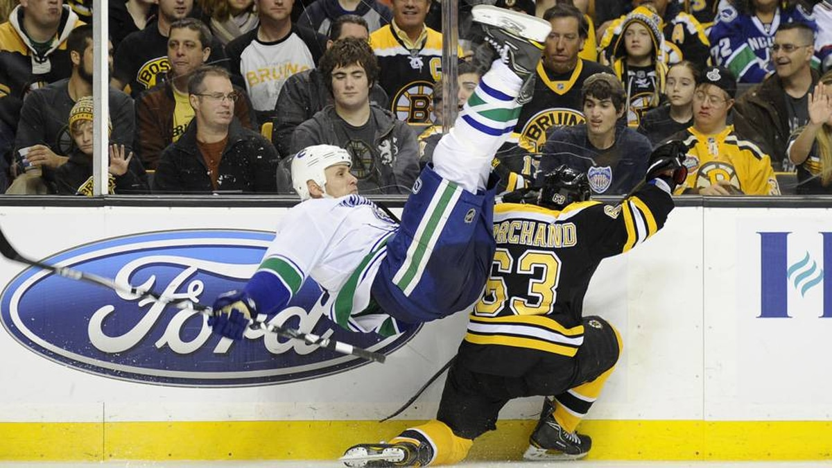 Boston Bruins left wing Brad Marchand upends Vancouver Canucks defenceman Sami Salo during the second period at TD Garden in Boston on Saturday.