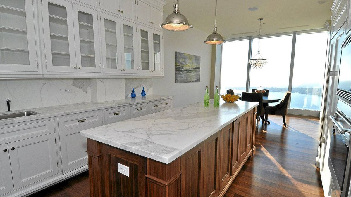 The bright white kitchen has stainless steel appliances, a large built-in refrigerator, a centre island of walnut wood and marble countertops.