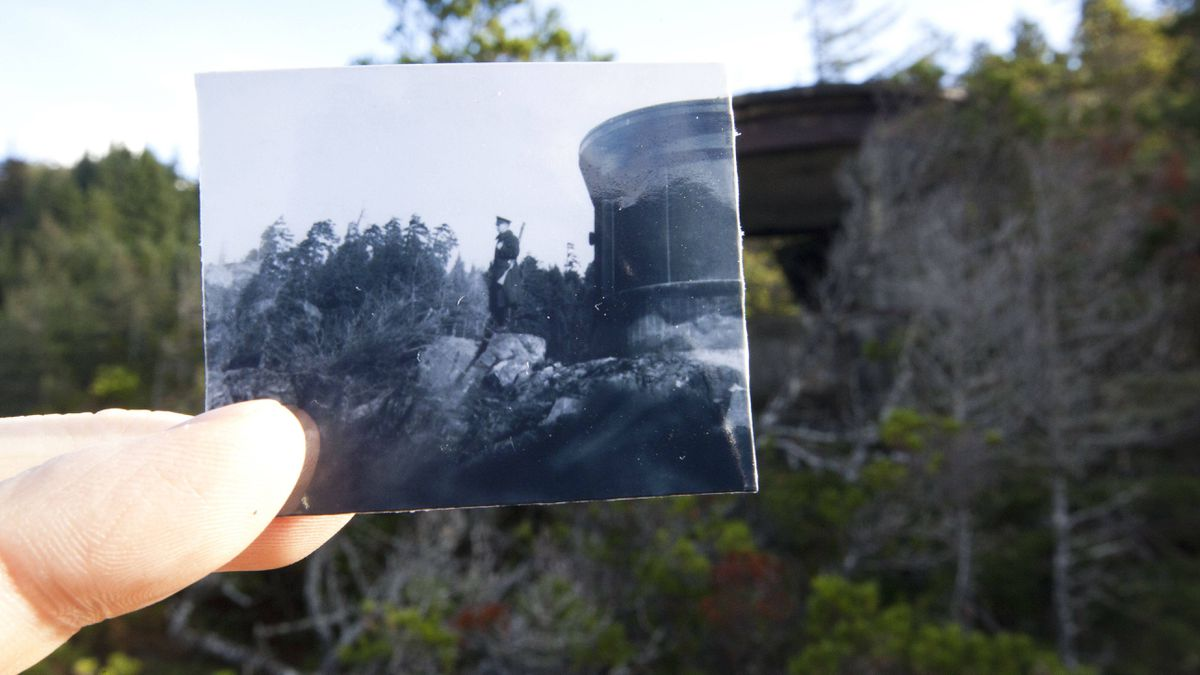 An old photo of a searchlight emplacement on Yorke Island is held up in the same spot more than 70 years later on Nov. 7, 2011.