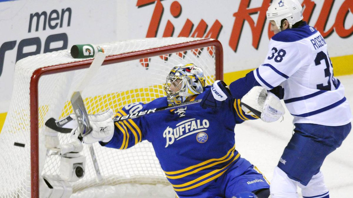 Buffalo Sabres goalie Ryan Miller, left, and Toronto Maple Leafs winger Jay Rosehill, right, reach for the puck during the first period of an NHL hockey game in Buffalo, N.Y. on Saturday, Feb. 5, 2011. The Sabres won 6-2. (AP Photo/Don Heupel)