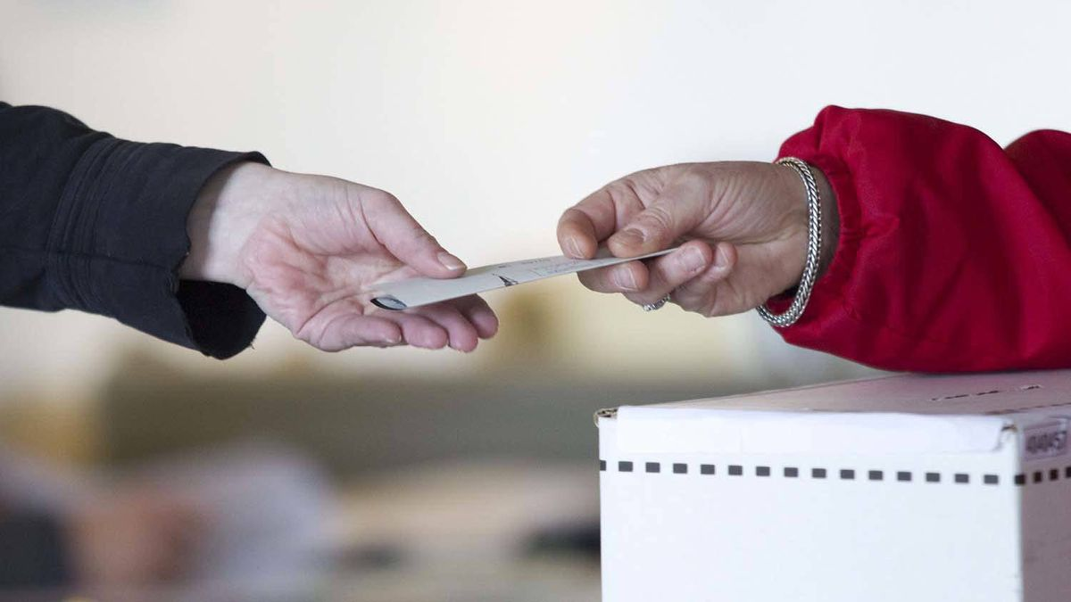 An election official hands back to a voter her marked ballot to place in the ballot box at a polling station on Toronto's Ward Island on Monday.