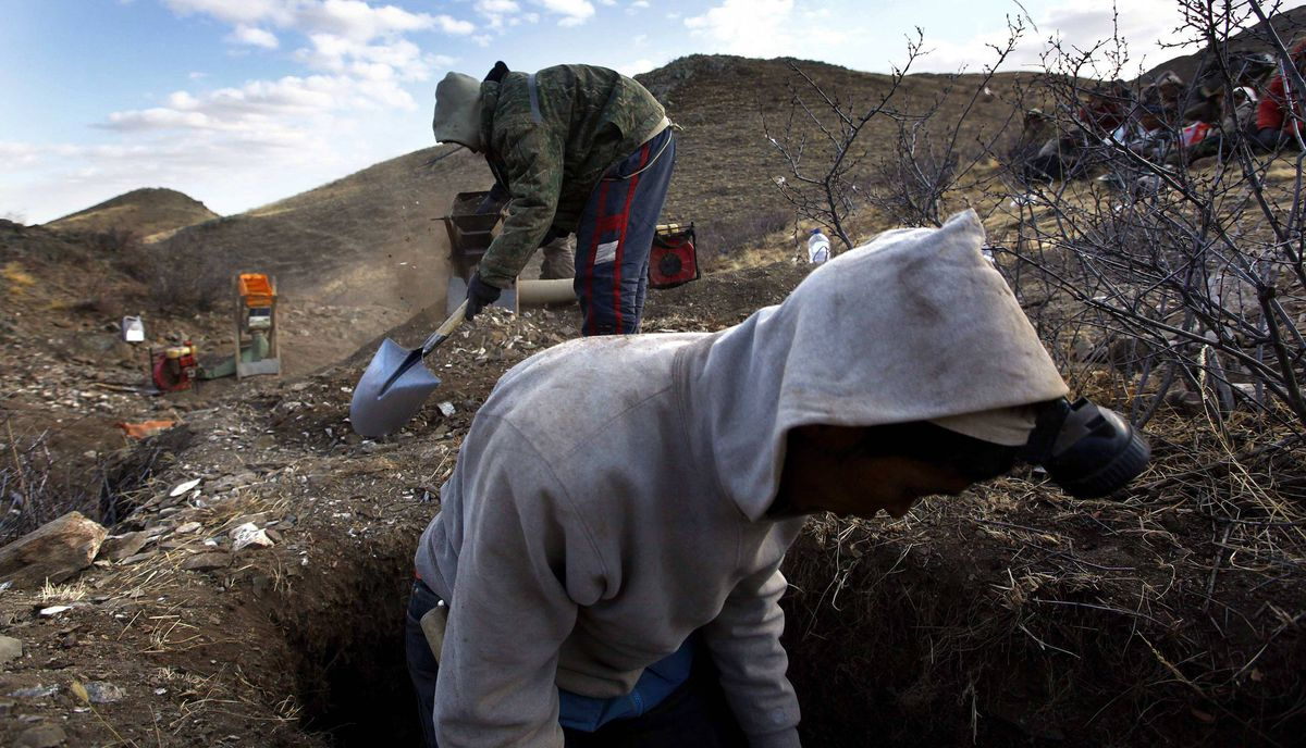 Small-scale miners dig holes searching for gold on a small hill overlooking grasslands located around 200 km south-west of the Mongolian capital city Ulan Bator.