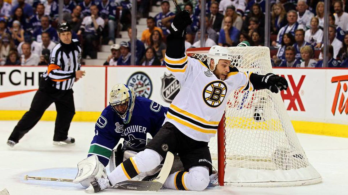 Gregory Campbell of the Boston Bruins falls after taking a shot against Roberto Luongo of the Vancouver Canucks.