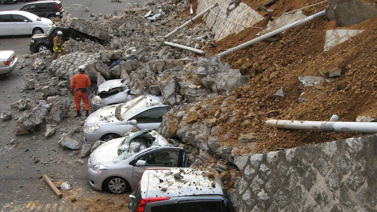 Vehicles are crushed by a collapsed wall at a car park in Mito city, Japan. Jiji Press/AFP/Getty Images
