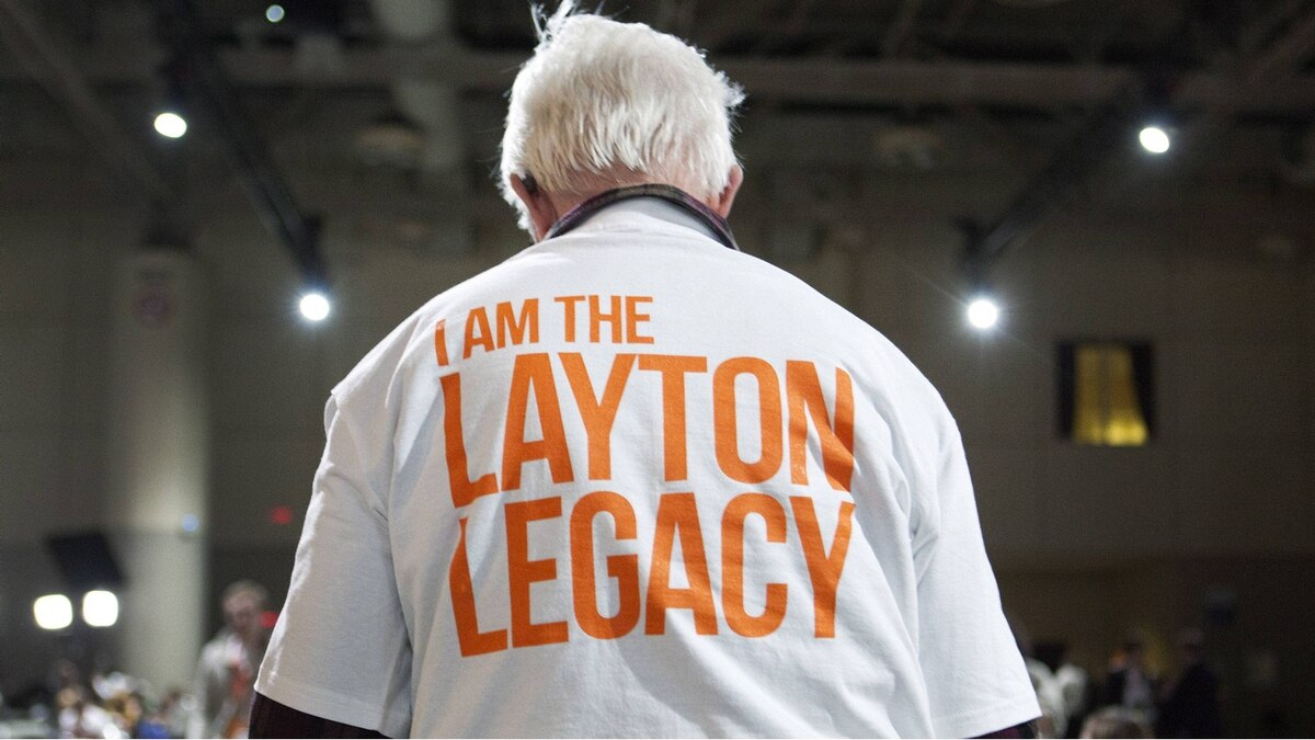 A man walks the room as people get ready to watch a special tribute to NDP leader Jack Layton, who passed way last year, during the NDP leadership convention in Toronto on Friday, March 23, 2012.