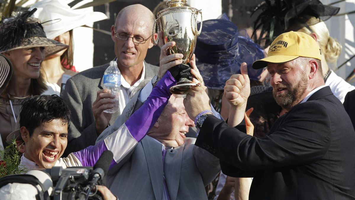 Jockey Mario Gutierrez , left, owner J. Paul Reddam , middle, and trainer Doug O'Neill hold the trophy after I'll Have Another won the 138th Kentucky Derby horse race at Churchill Downs Saturday, May 5, 2012, in Louisville, Ky. (AP Photo/Mark Humphrey)
