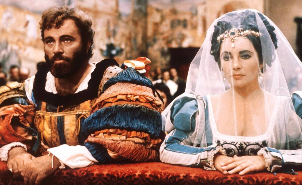 Elizabeth Taylor and Richard Burton kneel in a scene from the 1967 film The Taming of the Shrew in Italy.