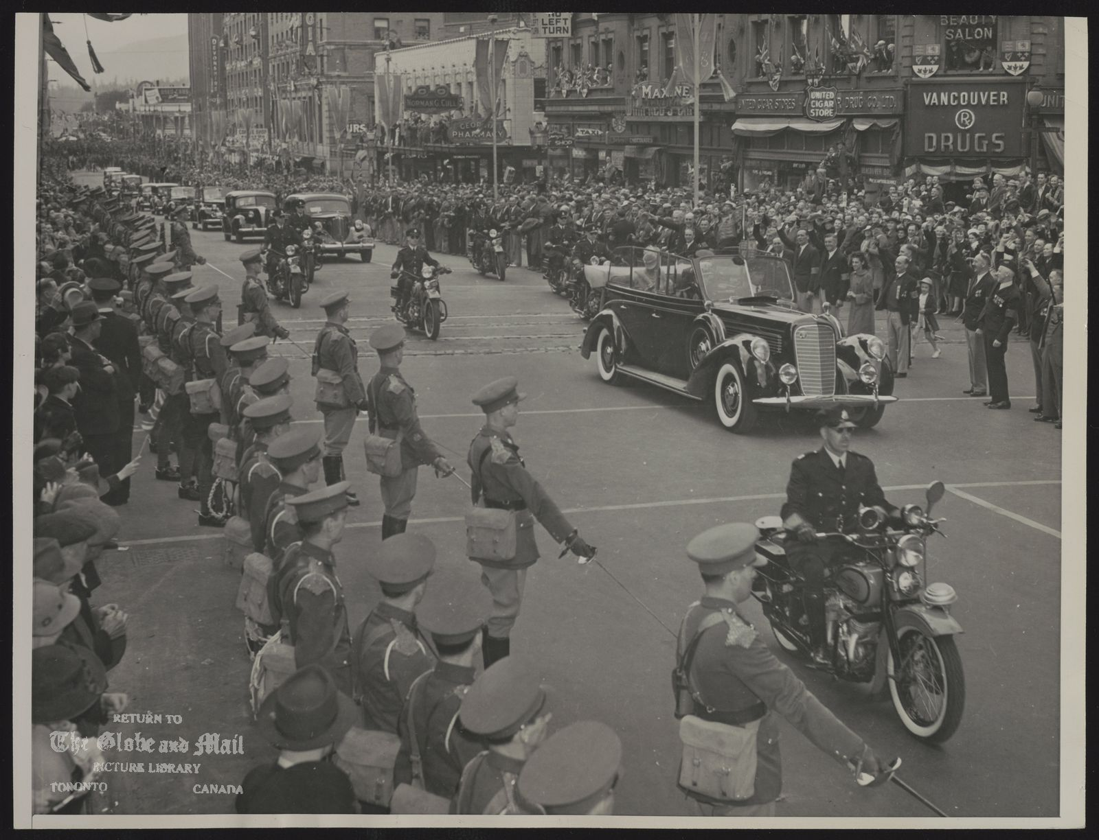 The notes transcribed from the back of this photograph are as follows: ROYAL FAMILY GREAT BRITAIN KING GEORGE VI & QUEEN ELIZABETH VISIT TO CANADA, 1939 BRITISH COLUMBIANS GREAT ROYAL PAIR. King George VI and Queen Elizabeth were greeted by massed thousands in downtown Vancouver, B.C., May 29, [1939] on their 52-mile tour of the city.