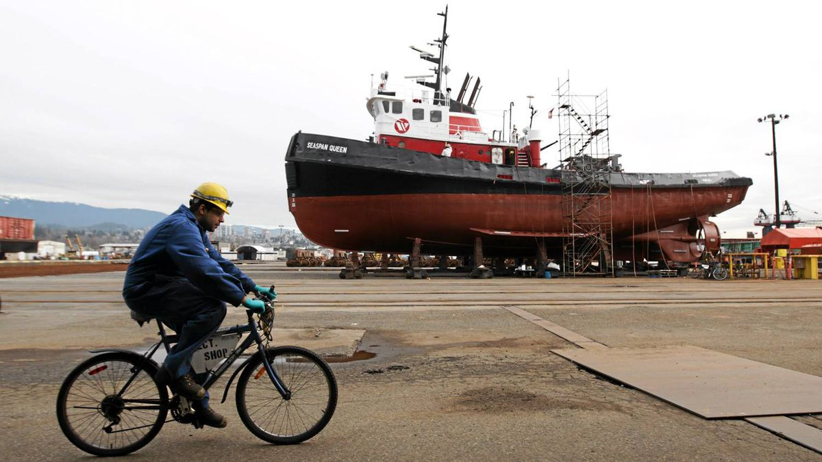 A worker rides a bicycle past the Seaspan Queen tugboat undergoing maintenance at Washington Marine Group Shipyards in North Vancouver, B.C., on Wednesday February 2, 2011.