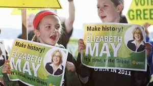 Young Green Party supporters hold signs during the kick-off of Elizabeth May's election campaign in Saanichton, near Victoria, on March 26, 2011.