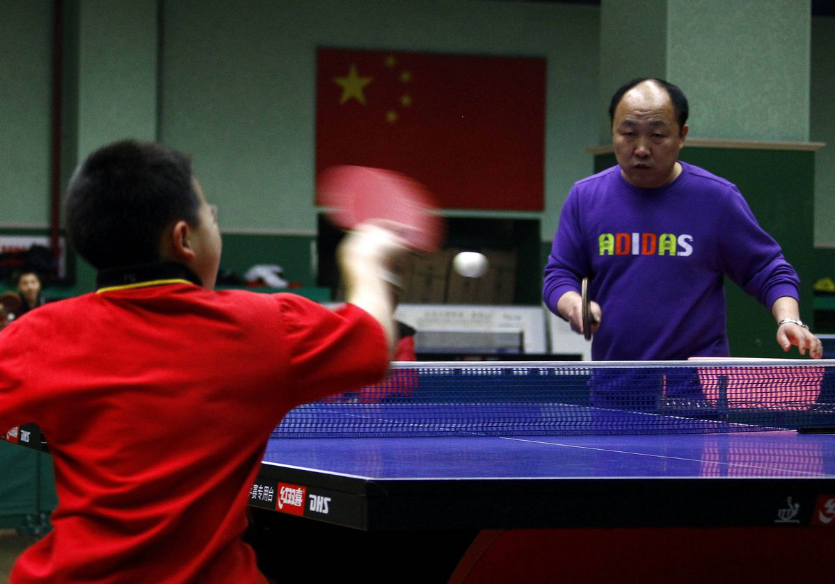 A coach watches as a student hits a shot during a table tennis class at the Shichahai Sports School in Beijing.