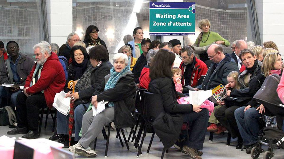 People sit in a waiting area for turn to be injected with the H1N1 flu vaccine at a clinic in Ottawa.
