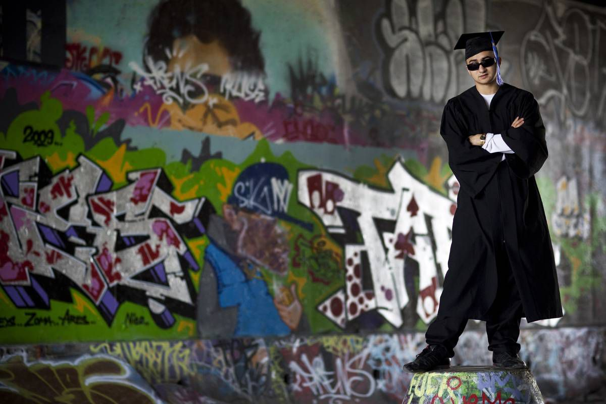 Graduate Justin Tolentino stands at a tunnel decorated with his graffiti. He had been kicked out of 10 different high schools.