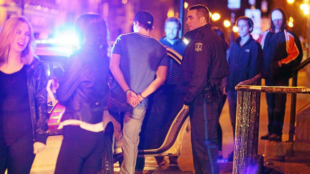 Police officers place one of two intoxicated young males into a cruiser outside of a popular pub in Halifax, Nova Scotia, April 20 , 2012.